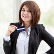Closeup portrait of cute young business woman smiling while holding credit card — Stock Photo #31409047