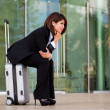 Young business woman sitting on suitcase — Stok fotoğraf