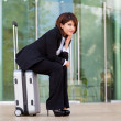 Stock Photo: Young business woman sitting on suitcase