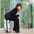 Young business woman sitting on suitcase — Stock Photo