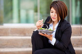Business woman eating a lunch outdoor — Stock Photo