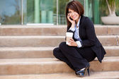 Young smiling business woman sitting on stairway calling with cellphone and holding a cup of coffee — Stock Photo