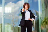 Smiling young business woman pointing with a finger — Foto Stock