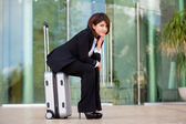 Young business woman sitting on suitcase — Stockfoto