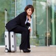 Young business woman sitting on suitcase — Stock Photo #31410123
