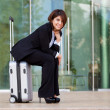 Young business woman sitting on suitcase — Foto de Stock