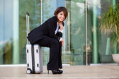 Young business woman sitting on suitcase — Стоковое фото