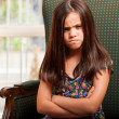 Sad little girl sitting on armchair — Stock Photo
