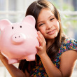 Stock Photo: Little girl with a piggy-bank