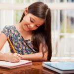 A little girl doing her homework — Stock Photo #32535335