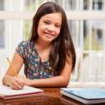 A little girl doing her homework — Stock Photo