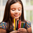 Cute girl holding colorful pencils — Stock Photo