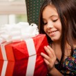 Cute little girl holding a gift — Lizenzfreies Foto