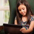 Little girl using Tablet PC in armchair — Stock Photo