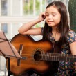 Little girl playing guitar at home — Stok fotoğraf