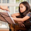 Little girl playing guitar at home — Stock Photo #32535507