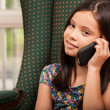Little girl is talking on a cell phone sitting in armchair — Stock Photo
