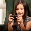 Cute little girl holding cell phone — Stock Photo
