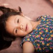 Little girl lying on the carpet — Stock Photo