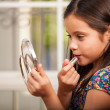Little girl trying painting her lips — Stock Photo