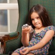 Little girl holding a remote control — Stockfoto