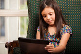 Little girl using Tablet PC in armchair — Foto de Stock