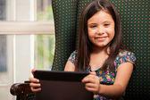 Meisje met behulp van tablet-pc in leunstoel — Stockfoto
