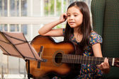 Little girl playing guitar at home — Stock Photo