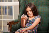 Little girl holding a remote control — Stock Photo