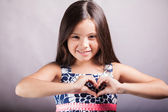 Little girl makes a gesture in the form of the heart. — Stock Photo