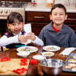 Siblings decorating Christmas cookies — Stock Photo
