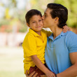 Father kissing his son outdoors — Stock Photo #34549357