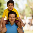 Son sitting on father shoulders — Stock Photo