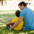 Father and his son are sitting on grass — Stock Photo