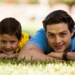 Man and his son lying on the grass — Stock Photo