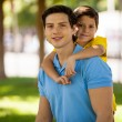 Boy riding piggy back on his father's back — Stock Photo #34549443
