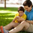 Father and his son using phone outdoors — Stock Photo