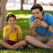 Father and his son eating sandwiches — Stock Photo