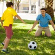 Father playing football with his son — Stock Photo #34549675