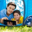 Father with his son using tablet in their tent — Foto de Stock