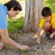 Boy playing marbles with his father — Stock Photo