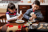 Boy and girl putting frosting on some holiday cookies — Stock Photo