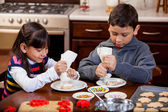 Siblings putting frosting on some holiday cookies — Stock Photo