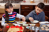 Girl and her brother baking cookies — Stock Photo