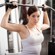 Girl shakes muscle simulator — Stock Photo #37045409