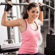 Girl shakes muscle simulator — Stock Photo #37045447