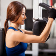 Girl shakes muscle simulator — Stock Photo #37045479