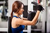 Girl shakes muscle simulator — Stock Photo