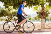 Cool sporty guy riding a bike — Stock Photo