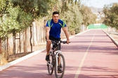 Latin man riding a bike — Stock Photo